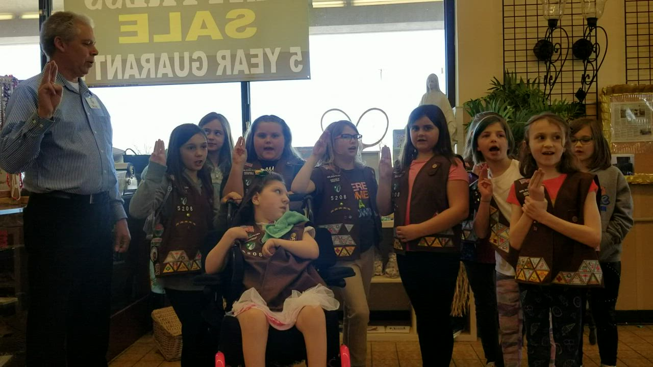 New Lenox Girl Scout Troop 75208, along with honorary Girl Scout Ron Moore, store manager of St. Vincent de Paul thrift store on Jefferson Street in Joliet, welcome a special needs girl into the troop.