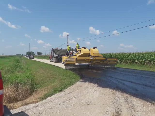 The chip spreader makes its way down Walker Road on Wednesday, Aug. 22, as part of the tar and chip process.