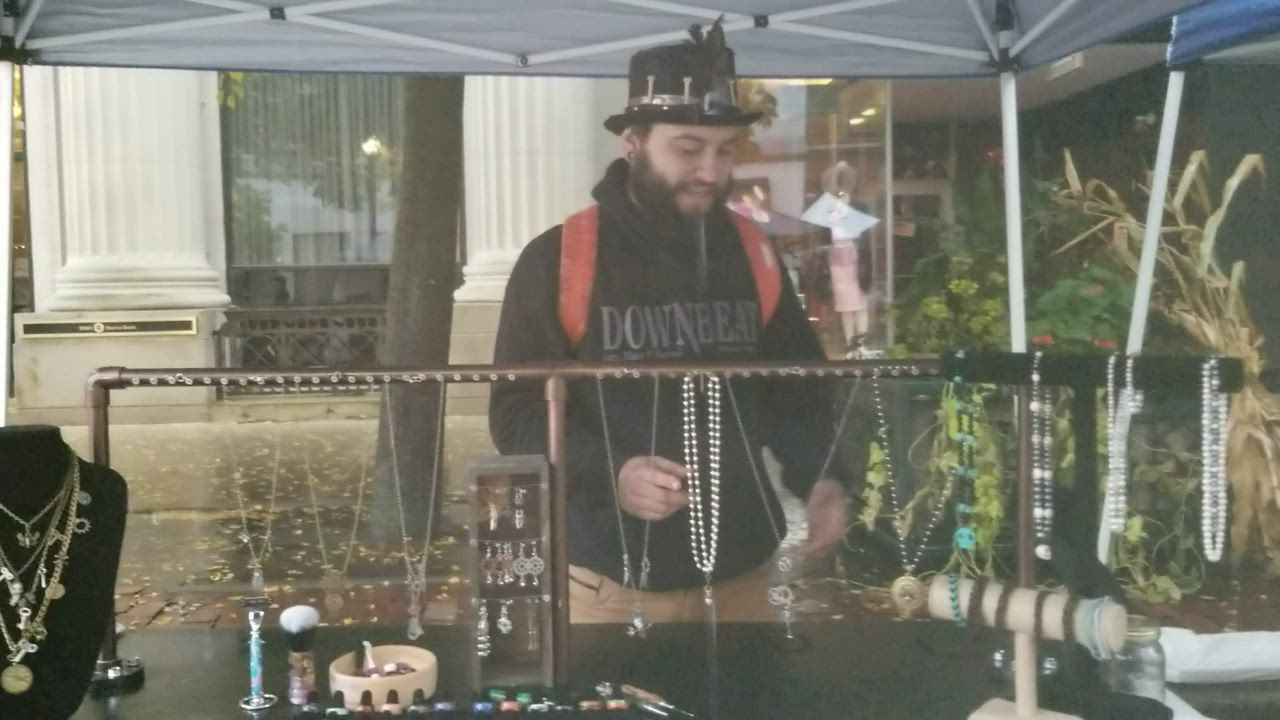 "At Joliet's first ""Panic at the Plaza"" event today, Voodoo Creations doesn't mind a bit of dramatic weather, and a representative shows off a variety of wood-turned projects."