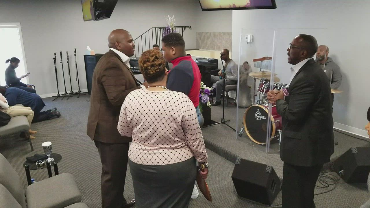 Jonas Jones, pastor at New Covenant Worship Center in Joliet, shares a song with his son, Jonas Jones Jr. while the duo's wife and mother Vinice Jones watches.