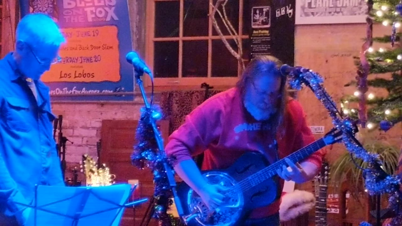 """Dave Ramont, left, and Dave Nelson, right, perform """"Silent Night"""" Dec. 23 at a holiday concert at Kiss The Sky record store in Batavia They organized the concert with fellow musician Gerald Dowd."""